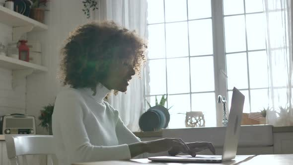 Cute AfricanAmerican Woman Enjoys the Good News Typing on a Gray Notebook