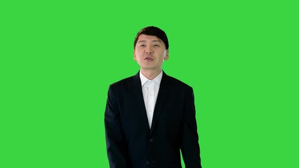 Asian Man in Suit Walking and Speaking on a Green Screen Chroma Key
