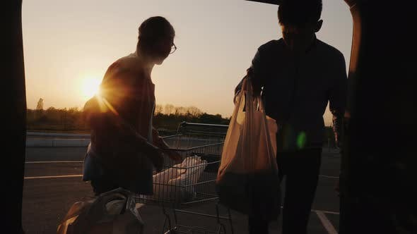 Thumbnail for A Man and a Woman Are Unloading Purchases From a Trolley in the Trunk of a Car. Buying Food