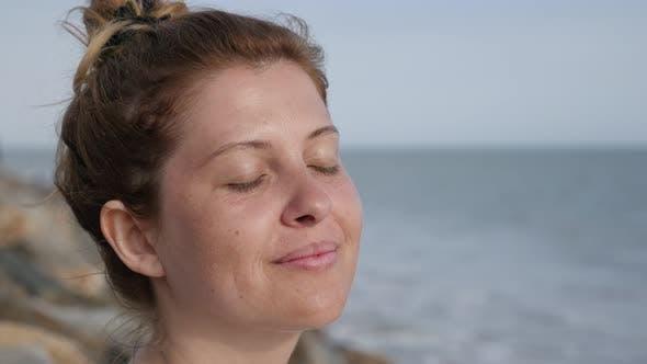 Thumbnail for Young beautiful female on ocean coast relaxing Caucasian blonde  woman enjoying beach sun by meditat