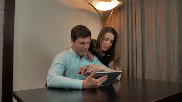 Attractive Couple Surfing on Digital Pad at Home