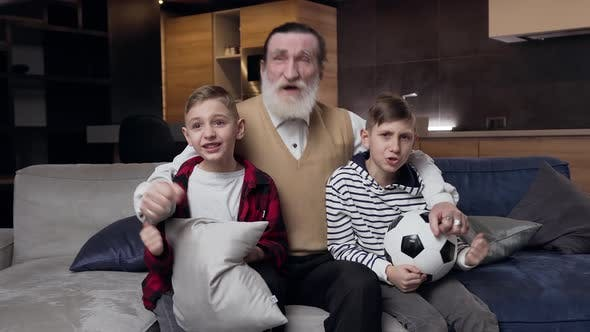 Thumbnail for Grandpa with Emotional Teen Grandsons which Revisioning the Football Match on TV