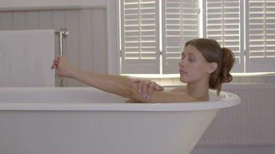 Woman taking bath in domestic bathroom
