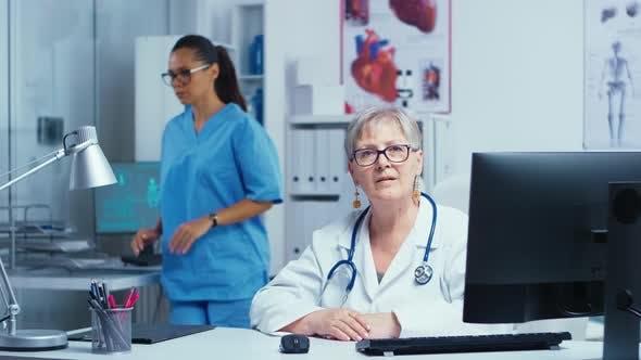 Erfahrene Senior Lady Doctor lächelnd vor der Kamera