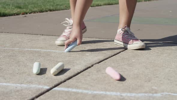 Thumbnail for Young girl playing Hopscotch at park, drawing with chalk, closeup