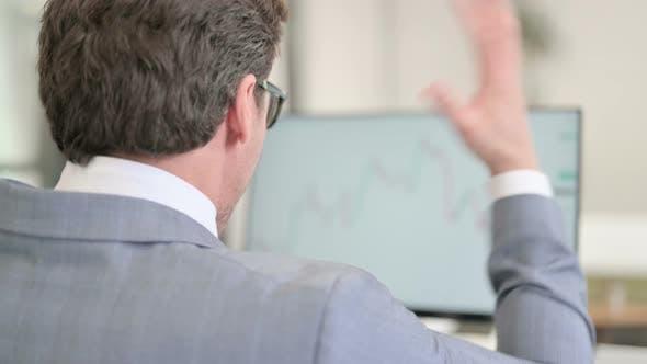 Businessman Looking at Charts on Desktop