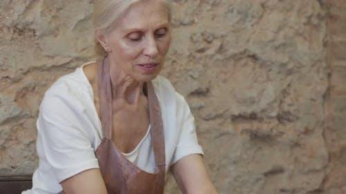 Senior Female Potter Sculpts a Clay Pot