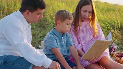Mom Reading Fairy Tale to Boy in Nature