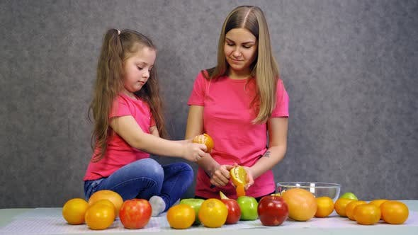Thumbnail for Happy family in the kitchen. Mother and child daughter preparing fruit