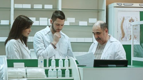 Team of pharmacists working at pharmacy drugstore senior