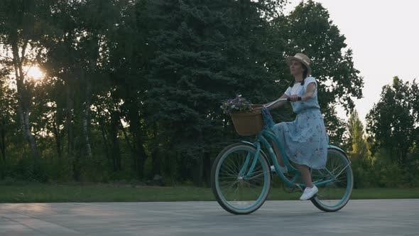 Thumbnail for Young brunette woman is cycling on vintage bicycle in city park at sunset.