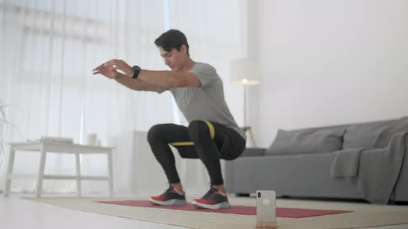 Young Man Athlete Exersices With Resistance Band. Fitness Trainer Doing Stretching Squats With