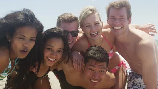 Thumbnail for Group portrait of young interracial friends huddled enjoying the beach