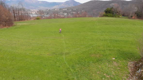 Aerial view: one cyclist riding mountain bike in the countryside on the Alps