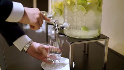 Men's Hands Pour Water Into a Glass From a Glass Decanter with Lemon and Lime