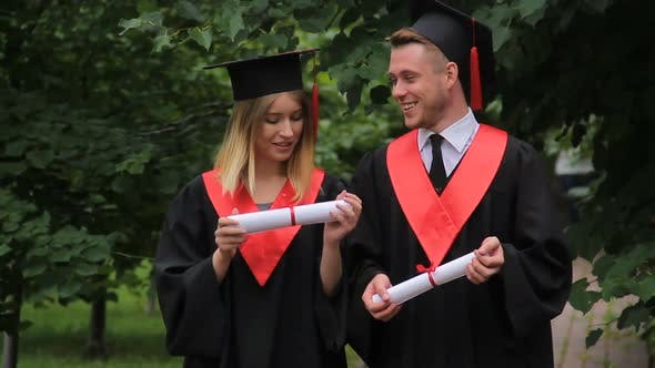 Cover Image for Woman and Man in Academic Dresses Holding Diplomas Talking and Walking in Park