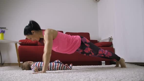 Thumbnail for Woman Doing Push-ups and Kissing Her Child at Home