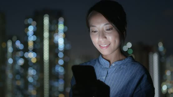 Thumbnail for Woman Check on Cellphone in City at Night
