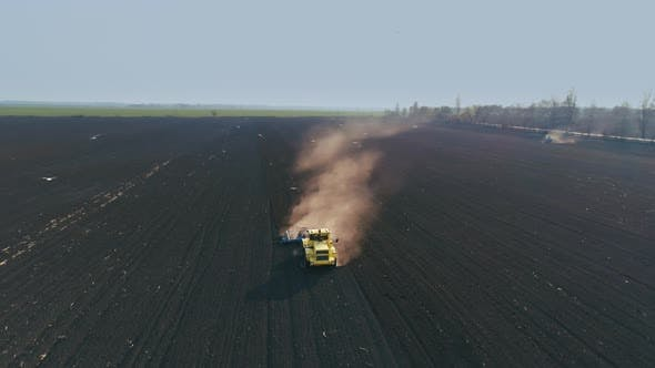 Thumbnail for Tractor in the Large Brown Field Prepares the Soil for Sowing. Flight Around