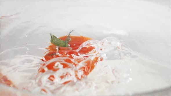 Cover Image for Single Red Ripe Tomato with Green Leaves Falls Under Water