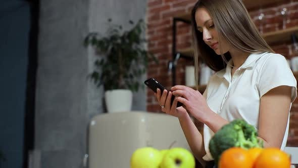 Thumbnail for Woman Browsing on Mobile Phone at Home Kitchen, Young Woman Browsing on Smartphone Smiling Happy