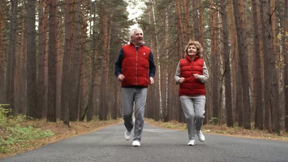 Thumbnail for Aged Man and Woman Running in Forest