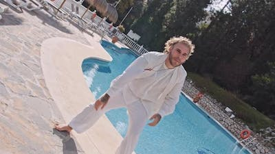 Man Dancing In White By Outdoor Swimming Pool