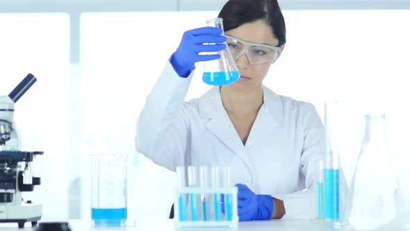 Thumbnail for Scientist, Doctor Looking at Blue Solution in Flask in Laboratory