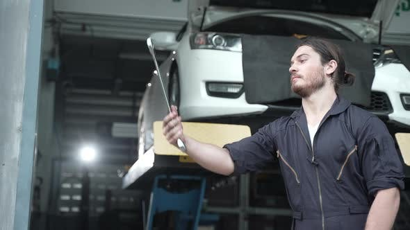 Car mechanic showing skill to control hand tools for car repair, an Auto mechanic working