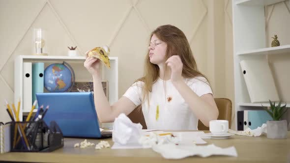 Thumbnail for Young Woman Scratching Head and Eating Pizza As Sitting in Front of Laptop