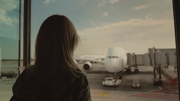 Thumbnail for Silhouette of a Young Woman Looking Through a Large Window on an Airliner