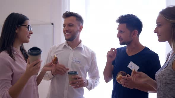 Thumbnail for Happy Creative Team Kommunizieren und trinken Kaffee mit Zimtbrötchen während der Pause im Büro
