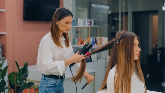 Professional Hair Straightening in a Beauty Salon. Beautiful Young Woman at a Reception in a Beauty