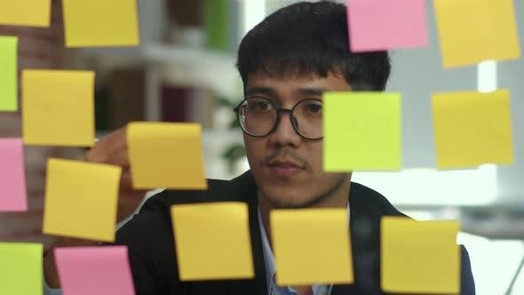 Asian creative man stick a sticky note on glass board.