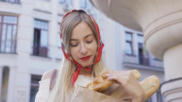 Thumbnail for Portrait of Beautiful Young Woman Standing on the Street Holding Freshly Baked Bread and Croissant