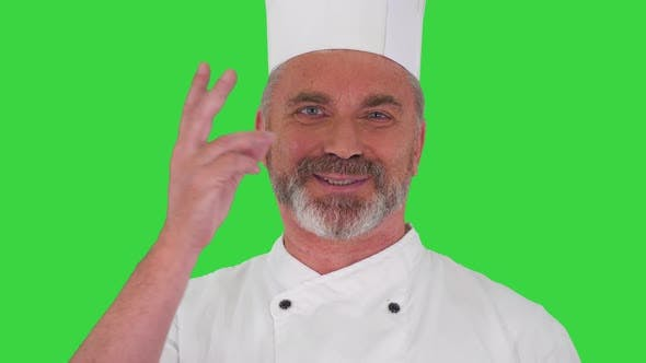 Elderly Professional Chef Man Showing Delicious Gesture To Camera on a Green Screen Chroma Key
