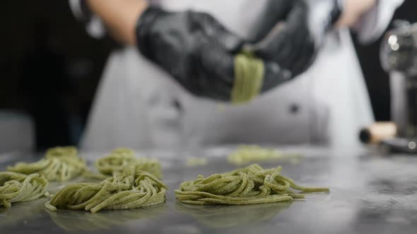 Thumbnail for Making Homemade Pasta. Female Hands Twisting and Putting Uncooked Raw Spaghetti or Tagliatelle
