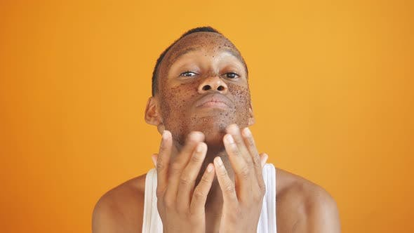 Black Guy Applies Cosmetic Scrub To His Face Man Wants Wellgroomed Face Isolated Yellow Background