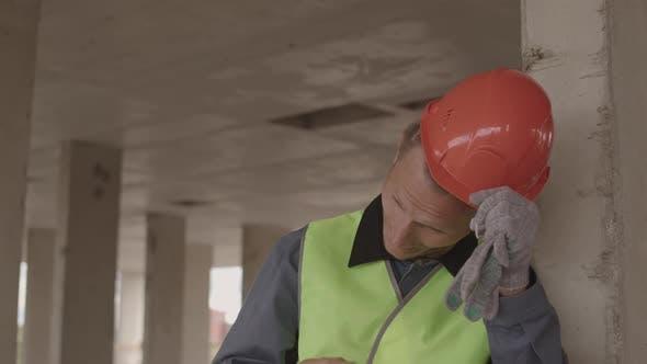 Tired Construction Worker Taking off Helmet