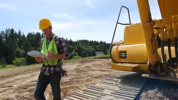 Worker inspecting excavation equipment