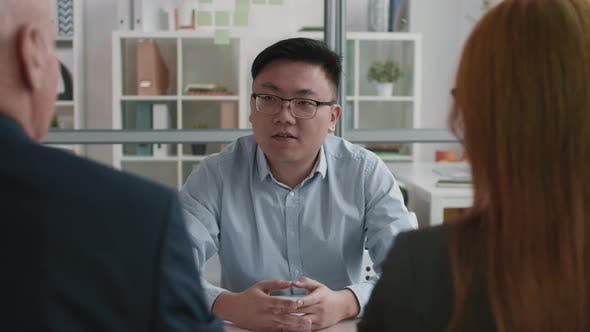 Unrecognizable Managers Interviewing Confident Asian Applicant