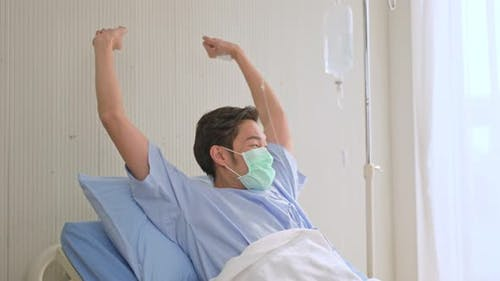 Unwell young Asian male patient lying down in hospital bed recovery after fell ill with cold and flu