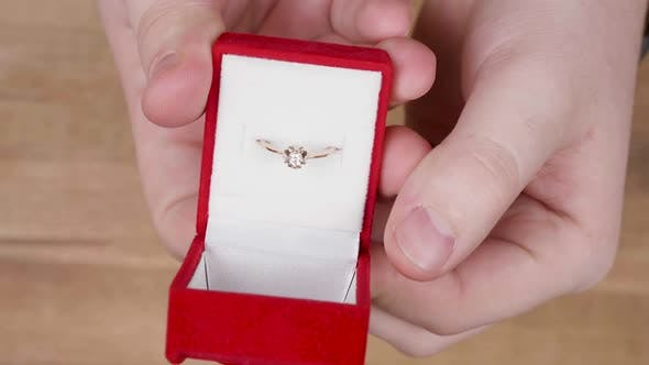 Cover Image for Hands of a Male Opening a Wedding Ring Box Before Proposal