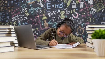 Girl kid studying and writing with headset