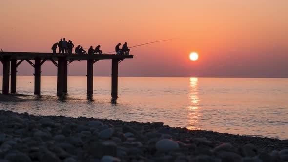 Thumbnail for Silhouettes of Fishermen with Fishing Rods at Sea Sunset Sitting on the Pier. Slow Motion.