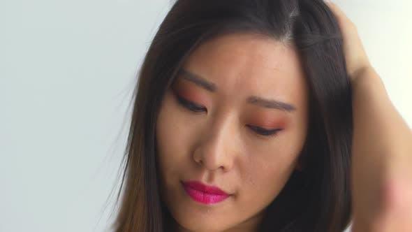 Thumbnail for Asian woman running hand through hair