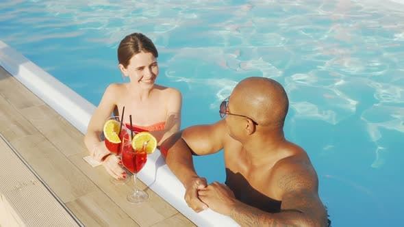 Thumbnail for Happy Multiethnic Couple Clinking Glasses in the Swimming Pool
