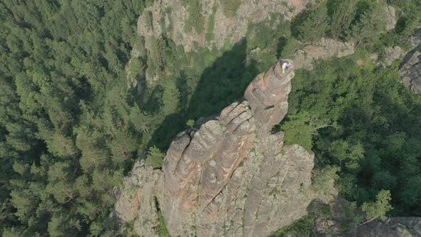 Aerial View of Two Men Standing on Top of a Mountain in the Forest in Summer.