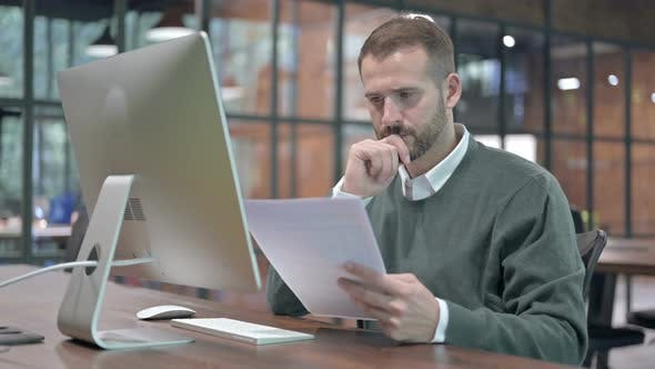 Thumbnail for Ambitious Man Reading Document on Office Desk