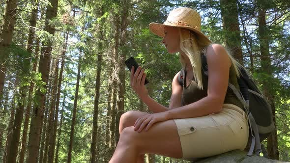 Thumbnail for A Young Beautiful Woman Sits on a Rock in a Forest on a Sunny Day and Works on a Smartphone